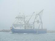A lone lobster boat leaves port at Cape Forchu, Nova Scotia, Canada.