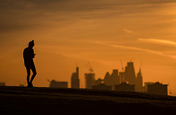 © Licensed to London News Pictures. 30/01/2018. London, UK. A jogger pauses on top of a frosty Primrose Hill as the sun rises. Photo credit: Peter Macdiarmid/LNP