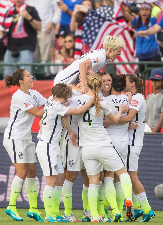 The United States's Megan Rapinoe jumps on top of her teammates as they celebrate Alex Morgan's goal during their FIFA Women's World Cup Group of 16 Match against Colombia at Commonwealth Stadium in Edmonton, Canada on June 22, 2015.   AFP PHOTO/GEOFF ROBINS