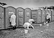 Natural theatre company dressed as toilet cleaners, perform in front of Andy Loos. Glastonbury 1994
