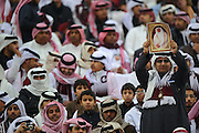 A fan of Qatar holds up a picture of The Emir of the State of Qatar, Hamad bin Khalifa Al Thani