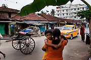 Razia Shabnam (in orange) waits for a taxi outside her apartment block with her son Saihaan, in Kidderpore, Calcutta, West Bengal, India as she leaves to referee an all-India invitational boxing competition in the neighbouring town of Burnpur. Razia Shabnam, 28, was one of the first women boxers in Kolkata. She was also the first woman in her community to go to college. She is now a coach and one of only three international female boxing referees in India. Photo by Suzanne Lee for Panos London