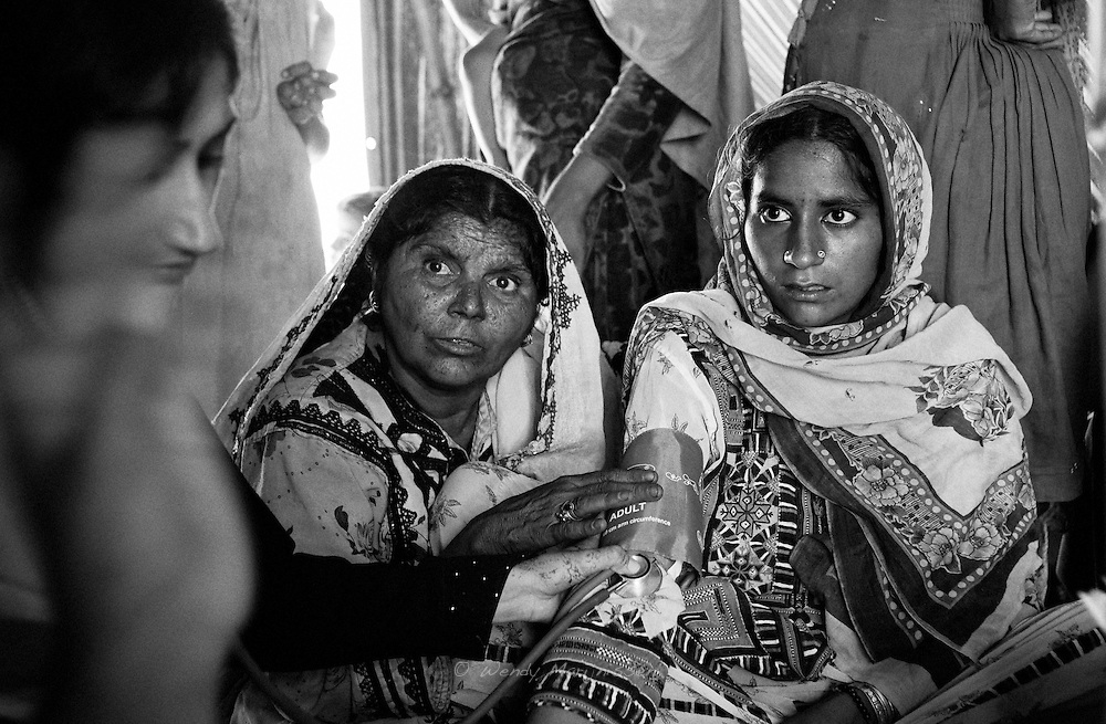 16 year old Shamira is pregnant and has her blood pressure checked by the midwife. Language barriers because of the many dialects and the illiteracy of many of the people living in the camps is causing extra stress to the women. Karachi, Pakistan, 2010