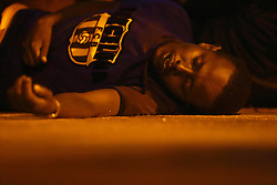 An exhausted would-be immigrant lies on the ground after disembarking from an Armed Forces of Malta (AFM) patrol boat at the AFM Maritime Squadron base at Haywharf in Valletta's Marsamxett Harbour early July 10, 2013. Sixty-eight African immigrants were rescued by the AFM, 70 nautical miles south of Malta from a vessel in distress while trying to reach European soil from Africa, according to army sources. REUTERS/Darrin Zammit Lupi (MALTA - Tags: HEALTH SOCIETY IMMIGRATION POLITICS) MALTA OUT. NO COMMERCIAL OR EDITORIAL SALES IN MALTA - RTX11IVD