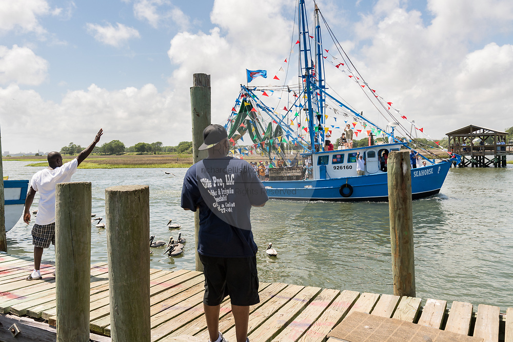 People watch a decorated shrimp boat parading down Shem Creek during the annual Blessing of the Fleet signifying the start of the commercial shrimping season April 30, 2017 in Mount Pleasant, South Carolina. Coastal shrimping is part of the low country heritage but has been declining rapidly with rising costs and increased foreign competition.
