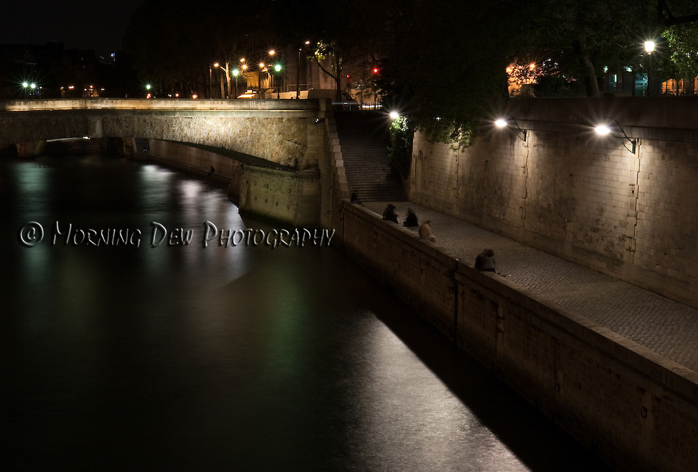 Groups of people gather along the bank of the Seine on a spring night in Paris.