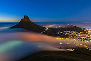 Dusk view of ocean fog flowing over Kloof Nek, past Lion's Head peak and into the city of Cape Town, South Africa.