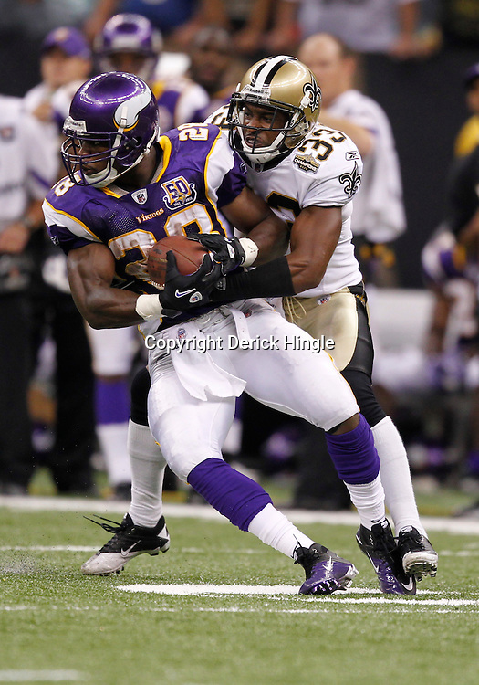 September 9, 2010; New Orleans, LA, USA;  Minnesota Vikings running back Adrian Peterson (28) is tackled by New Orleans Saints cornerback Jabari Greer (33) during the fourth quarter of the NFL Kickoff season opener at the Louisiana Superdome. The New Orleans Saints defeated the Minnesota Vikings 14-9.  Mandatory Credit: Derick E. Hingle
