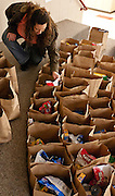 Dynette Harvey looks through food bags during the Deseret Media Corporation sponsored Toy Depot for selected families at Washington Elementary, Monday, Dec. 3, 2012.