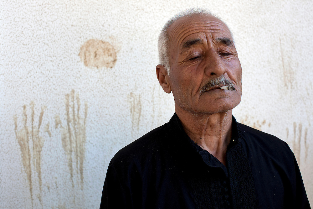 05/07/2013 near Damour, Lebanon: 70-year old Syrian refugee Abu Said smokes a hand-rolled cigarette outside of the apartment where he has relocated. Estimates have placed the number of Syrian refugees in Lebanon at well over 500,000 people.