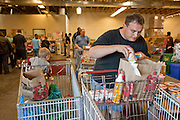 Apr. 3, 2009 -- MESA, AZ:  TIM HALL, from Tempe, AZ, picks up dairy products at the United Food Bank in Mesa, AZ. Hall said he drives a tourist bus but as the tourism and leisure industry has suffered in the recession his work in disappearing and in March he only work five days. A spokesperson for the United Food Bank in Mesa, AZ, said demand has increased by more than 100 percent in the last year. She said that at this time in 2008, about 175 people a week (the food bank is open one day a week) bought 200 boxes a food but now they were seeing about 350 people per week and they were buying 400-450 boxes of food per week. Each box of food cost $16 and contains enough food for five meals for two people, including meat, fruit and vegetables and starches. In addition to the food boxes, the food bank gives away perishables, like fresh baked goods and produce, that are donated by Phoenix area grocery stores and food producers. She said the number of donations to the food bank have increased as the economy has worsened but each donation is smaller and the gap between donations and what the food bank needs is widening.    Photo by Jack Kurtz / ZUMA Press