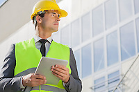 Young male architect with digital tablet looking away outside building