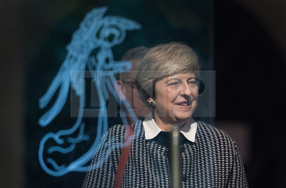 © Licensed to London News Pictures. 08/10/2017. Maidenhead, UK. Prime Minister Theresa May passes behind an image of an angel on the glass door of the church she attended in her constituency. Mrs May has faced heavy criticism after her disastrous conference speech, with some MPs in the Conservative party calling for her to stand down.  Photo credit: Peter Macdiarmid/LNP