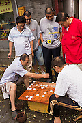 Men play Dou Shou Qi or Jungle, a traditional board game along a hutong in Beijing, China