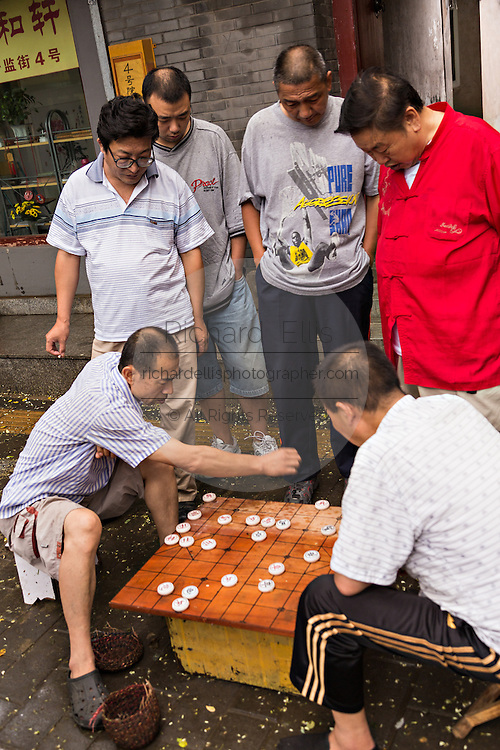 Men play Dou Shou Qi or Jungle, a traditional board game along a hutong in Beijing, China
