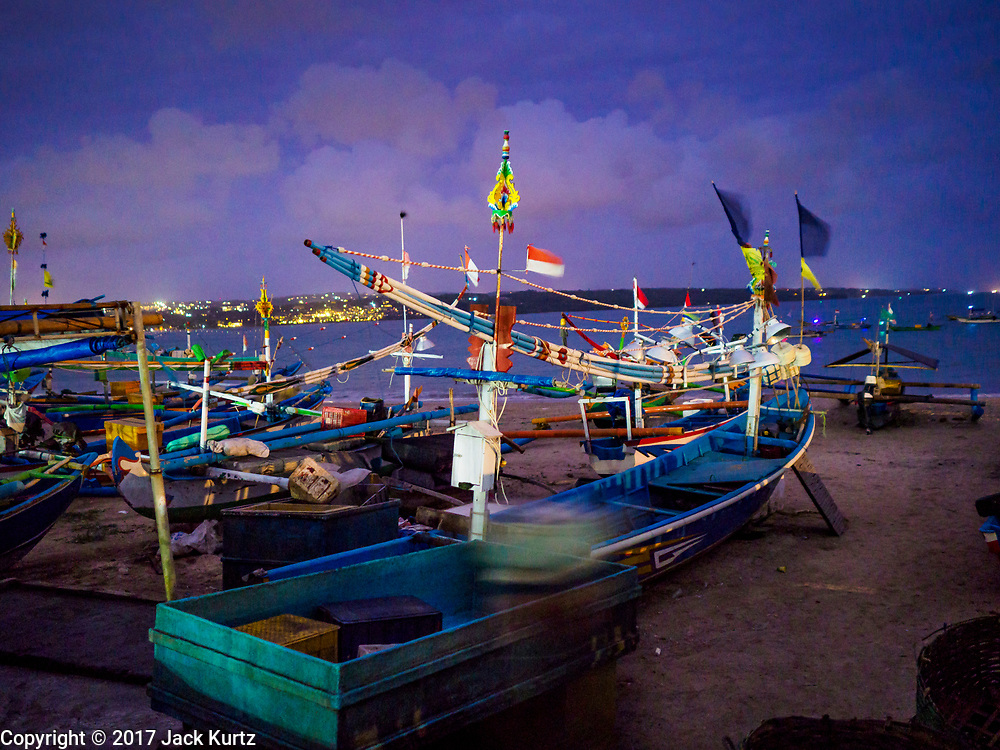 03 AUGUST 2017 - KUTA, BALI, INDONESIA: Fishermen's outrigger canoes before sunrise along Jimbrana Beach in Kuta. The beach is close to the airport and a short drive from other beaches in southeast Bali. Jimbrana was originally a fishing village with a busy local market. About 25 years ago, developers started building restaurants and hotels along the beach and land prices are rising. The new emphasis on tourism is changing the nature of the area but the fishermen are still busy very early in the morning.     PHOTO BY JACK KURTZ