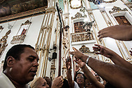 In the sanctuary of Bomfim, during the morning mass, everyone wants to touch the crucifix.