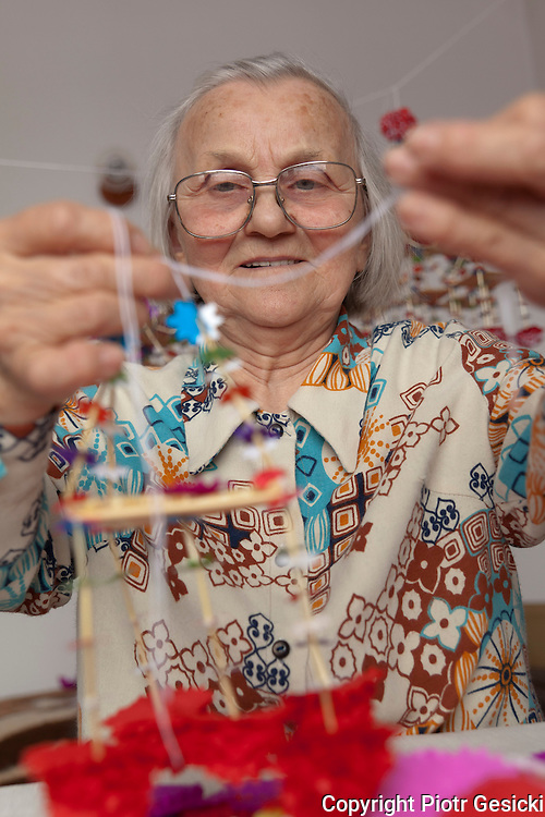 Old folk artist Maria Lasota creating  traditional straw spiders to decorate interiors of huts and houses especially in Christmas and Easter time