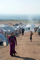Syrian refugees walk outside their basic tents at a camp for internally displaced persons in Atmeh, Syria, adjacent to the Turkish border.