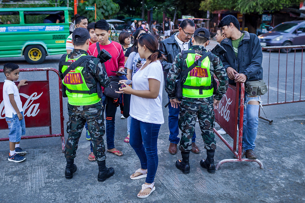 Davao City, Mindanao, Philippines - JUNE 18: Members of the Davao Task Force Army check visitors at the entrance of Roxas Night Market.  Roxas Night Market was bombed on September 16, 2016.  14 people were killed and 70 were injured and three men who are linked to the Maute Group were arrested for the bombing.