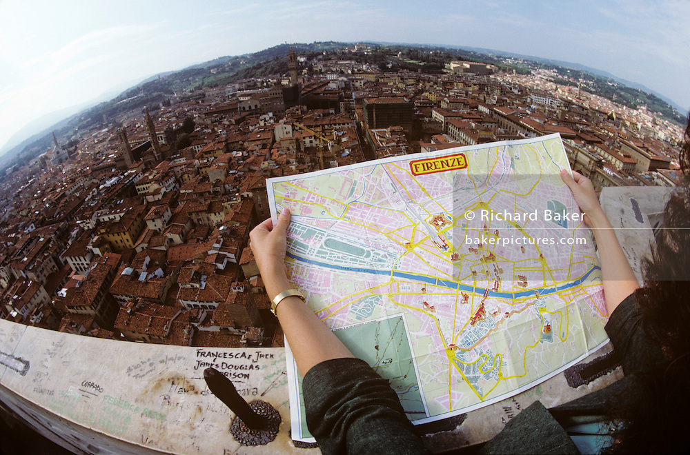 Seen through a fisheye lens, we see an aerial view of the city of Florence (Firenze) as a lady tourist surveys the urban landscape using a tourist map. She has climbed the 84.7 meters (277.9 ft) high Gioto's Belltower (or campanile) of Duomo Cathedral. Due to the nature of the extreme-wide lens, the curvature of the horizon makes a global sort of perspective. Far below are the tiled rooftops of this Italian city's housing and properties and further into the distance are the green fields of Tuscany. On the marble ledge that is unguarded against accidental or intentional leaps, there is the graffiti of world tourism. The languages of world youth are written on this Renaissance building. The Basilica di Santa Maria del Fiore is the cathedral church (Duomo), begun in 1296 in the Gothic style to designs of Arnolfo di Cambio and completed structurally in 1436