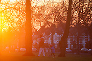 A child scoots with an adult as an urban sun sets, on 19th January 2017, in Ruskin Park, London borough of Lambeth, England.