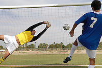 Goalkeeper reaching for ball as soccer player scores