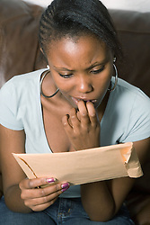 Teenage girl looking at exam result envelope,