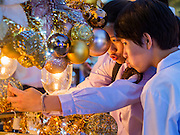 13 DECEMBER 2013 - BANGKOK, THAILAND: Thais take self portraits with their smart phone in the Christmas lights at Siam Paragon shopping center in the Ratchaprasong area of Bangkok. Thailand is overwhelmingly Buddhist. Christmas is not a legal holiday in Thailand, but Christmas has become an important commercial holiday in Thailand, especially in Bangkok and communities with a large expatriate population.      PHOTO BY JACK KURTZ