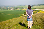 Woman standing on steep chalk scarp slope  Cherhill Down, Wiltshire, England looking towards the village of Cherhill in the clay vale