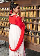 A Japanese woman wearing a kimono posing next to prayer boards at the Fushimi Inari Shrine, Kyoto, Japan
