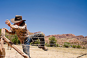 "June 16, 2008 -- COLORADO CITY, AZ: A member of the Jessop family jumps over the fence around their horse corral in Colorado City, AZ. The Jessops are a polygamous family and members of the FLDS. Colorado City and neighboring town of Hildale, UT, are home to the Fundamentalist Church of Jesus Christ of Latter Day Saints (FLDS) which split from the mainstream Church of Jesus Christ of Latter Day Saints (Mormons) after the Mormons banned plural marriage (polygamy) in 1890 so that Utah could gain statehood into the United States. The FLDS Prophet (leader), Warren Jeffs, has been convicted in Utah of ""rape as an accomplice"" for arranging the marriage of teenage girl to her cousin and is currently on trial for similar, those less serious, charges in Arizona. After Texas child protection authorities raided the Yearning for Zion Ranch, (the FLDS compound in Eldorado, TX) many members of the FLDS community in Colorado City/Hildale fear either Arizona or Utah authorities could raid their homes in the same way. Older members of the community still remember the Short Creek Raid of 1953 when Arizona authorities using National Guard troops, raided the community, arresting the men and placing women and children in ""protective"" custody. After two years in foster care, the women and children returned to their homes. After the raid, the FLDS Church eliminated any connection to the ""Short Creek raid"" by renaming their town Colorado City in Arizona and Hildale in Utah.   Photo by Jack Kurtz"