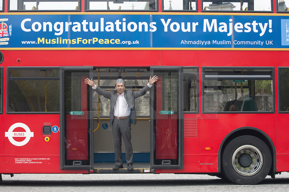"© licensed to London News Pictures. London, UK 10/05/2012. A muslim supporter of Diamond Jubilee posing with on a bus with has a banner reading ""Congratulations Your Majesty!"" outside Tower of London, today (10/05/12). Ahmadiyya Muslim Association and various charities launching a campaign to celebrate the Queen's Diamond Jubilee. The campaign will have 100 London buses with banners reading ""Congratulations Your Majesty!"" and a charity walk on this Sunday. Photo credit: Tolga Akmen/LNP"