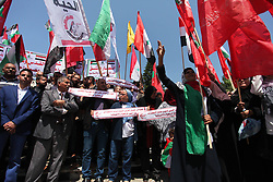 April 15, 2018 - Gaza City, Gaza Strip, Palestinian Territory - Palestinian protesters wave the flags during a protest against U.S. air strikes in Damascus, in Gaza city April 15, 2018  (Credit Image: © Mahmoud Ajour/APA Images via ZUMA Wire)