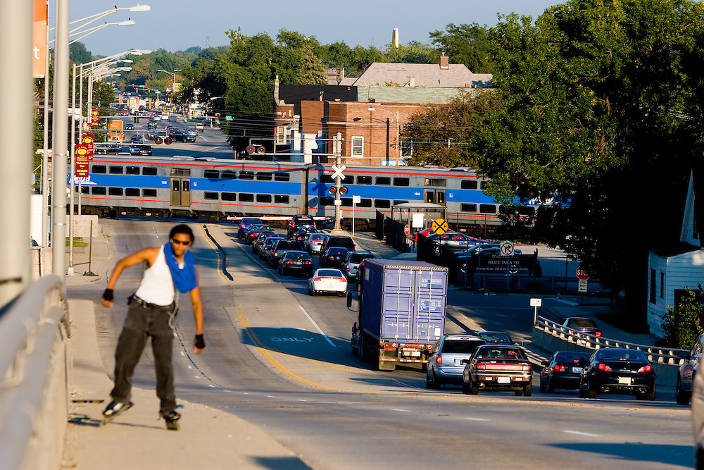 A rollerblader skates uphill on an overpass in Blue Island, IL, as a Metra Electric train crosses Burr Oak Ave, briefly tying up rush hour traffic.