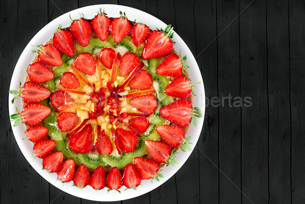 Fresh fruit pie decorated with strawberries, peaches and kiwi, on black wooden background, top view shot with copy space.