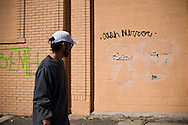 A man walks past a wall with the words Cash Mirror on them. Detroit has been badly hit by the economic crisis and signs are on the walls everywhere. Detroit, USA? 2011