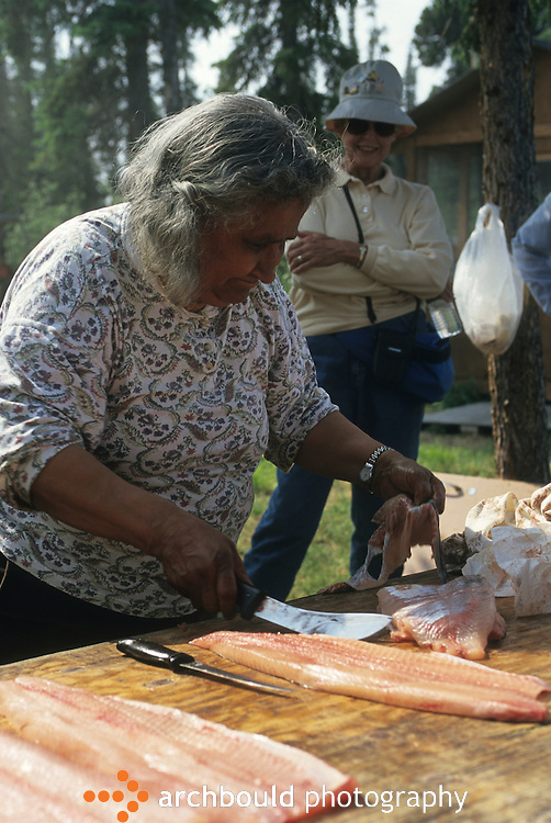 First Nation fish camp. Woman cleaning fish.
