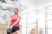 Dedicated woman lifting kettlebell in crossfit gym