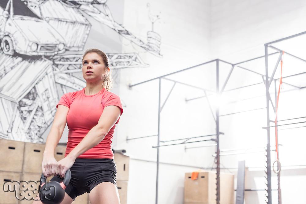 Dedicated woman lifting kettlebell in crossfit gym