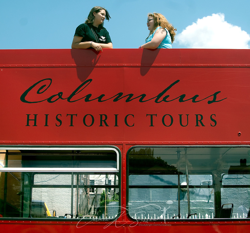 Adrianna White (left) and Danielle Martin chat as they stand on the top level of a double-decker tour bus parked outside the Tennessee Williams Welcome Center in Columbus, Miss. April 17, 2010. Rides are $8 and include stops at many of the historic, antebellum homes throughout the city. (Photo by Carmen K. Sisson/Cloudybright)