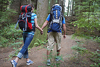 Couple holding hands walking in forest