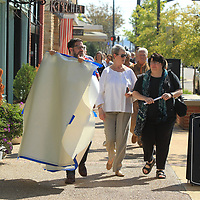 """Chandler Griffin, with Blue Magnolia Films, leads a group of Tupelo residents up main street to Renasant Bank to unveil more photos in downtown Tupelo on Thursday morning for theTupelo Bicentennial Photo Project unveiling. Blue Magnolia Films partnered with the city of Tupelo to tell eight stories from different points of view, all with the goal of """"Celebrating Storytelling,"""" a Mississippi bicentennial project that will culminate with 100 different stories by the end of the year."""