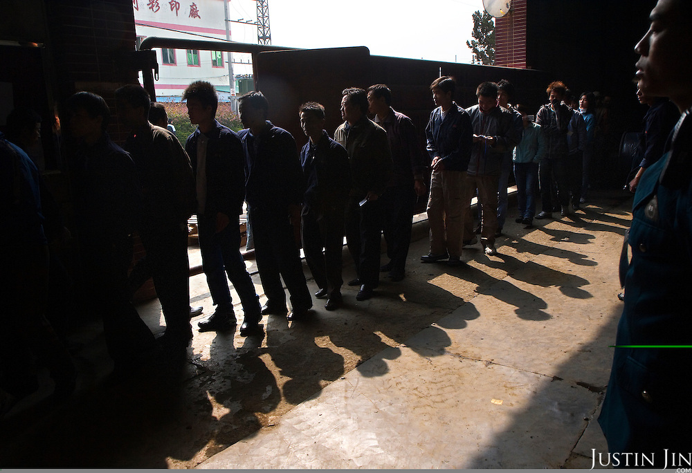 "Workers queue to exit the Grandsmart jeans factory in Zhongshan city, China. .This picture is part of a photo and text story on blue jeans production in China by Justin Jin. .China, the ""factory of the world"", is now also the major producer for blue jeans. To meet production demand, thousands of workers sweat through the night scrubbing, spraying and tearing trousers to create their rugged look. .At dawn, workers bundle the garment off to another factory for packaging and shipping around the world..The workers are among the 200 million migrant labourers criss-crossing China.looking for a better life, at the same time building their country into a.mighty industrial power."