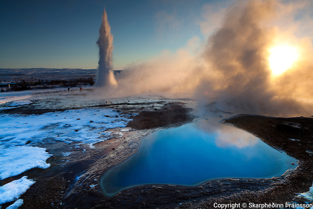 Geysir in Haukadalur, south-west Iceland. Erupting Strokkur with blue pool in foreground.