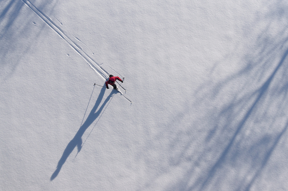 A single cross country skier casts a long shadow across a snow-covered field in central Oregon, as seen from an aerial perspective in late afternoon light.