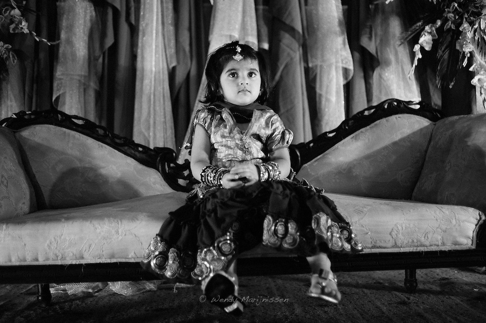 A little girl dressed up in festive clothes sits on the sofa reserved for the couple getting married. Lahore, Pakistan, 2009