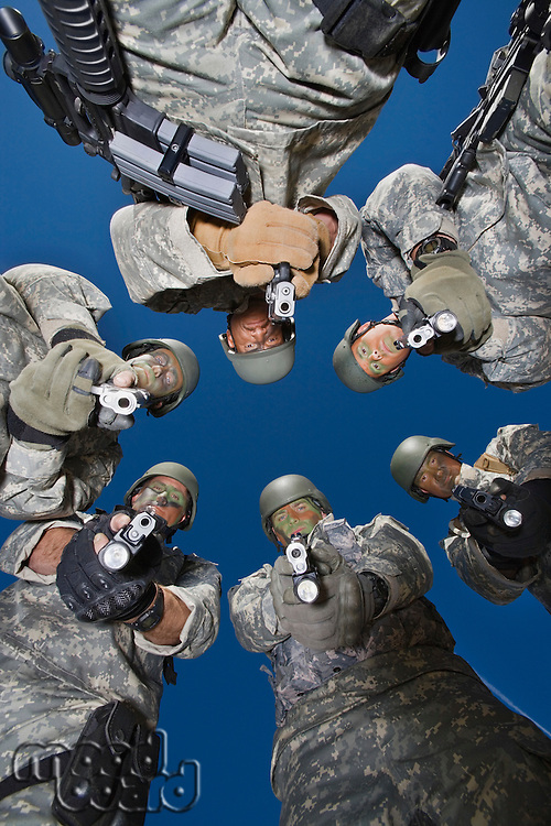 Low angle portrait of soldiers standing in circle, aiming