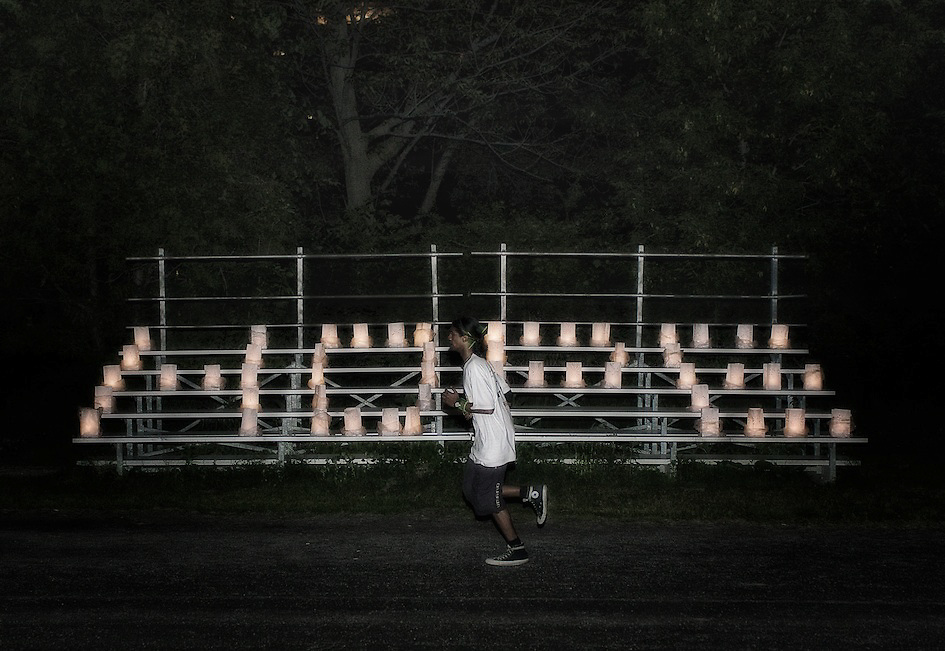 Photographer's Note: People make their way around the track lap after lap usually with a combination of running, walking, and some via wheelchair. In the last few minutes of the luminary ceremony, I snuck away and captured this image of a lone man running past the Hope bleachers.
