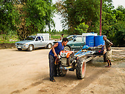 10 MAY 2016 - TA TUM, SURIN, THAILAND: A man starts his tractor after getting water from the artesian well in Ta Tum, Surin, Thailand. The well is the most important source of drinking water for thousands of people in the communities surrounding it.  In the past many of the people had domestic water piped to their homes or from wells in their villages but those water sources have dried up because of the drought in Thailand. Thailand is in the midst of its worst drought in more than 50 years. The government has asked farmers to delay planting their rice until the rains start, which is expected to be in June. The drought is expected to cut Thai rice production and limit exports of Thai rice. The drought, caused by a very strong El Nino weather pattern is cutting production in the world's top three rice exporting countries:  India, Thailand and Vietnam. Rice prices in markets in Thailand and neighboring Cambodia are starting to creep up.    PHOTO BY JACK KURTZ